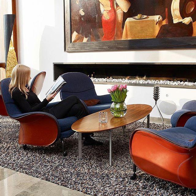 """I vår lobby hittar vi dessa sköna fåtöljer. Fåtöljen Lousiana är inspirerad av en hästsadel och är designad av Vico Magistretti från Milano. Tavlan är gjord utav konstnären Alexander Klingspor. Konstverket heter """"Avalon"""" och är speciellt framtagen till hotellet. Kom in och njut av en kopp kaffe vid brasan, välkomna! In our lobby we find these comfortable armchairs. The armchair Louisiana is inspired by a horse saddle, designed by Vico Magistretti from Milan. The painting is made of the artist Alexander Klingspor. The artwork is named"""